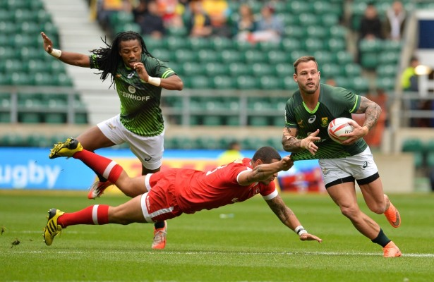 LONDON, ENGLAND - MAY 21: Francois Hougaard of South Africa is grabbed by Mike Fuailefau of Canada during the match between South Africa and Canada on day 1 of the HSBC World Rugby Sevens Series London at Twickenham Stadium on May 21 in London, South Africa. (Photo by Rodger Sedres/Gallo Images)